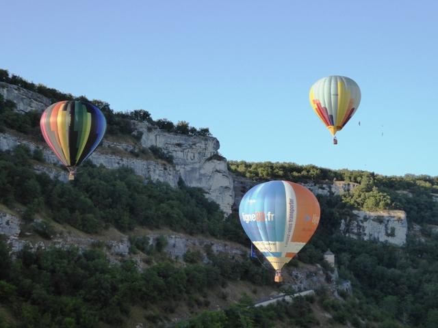 Three hot-air balloons take off