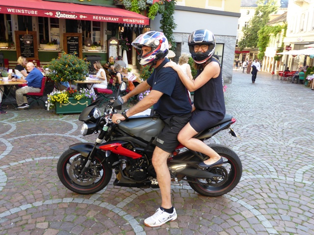 Manageress Patricia rides pillion to the  bike parking